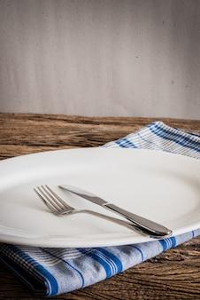 Biały talerz na serwetce i srebrnym widelcu, nóż. na drewnianym blacie