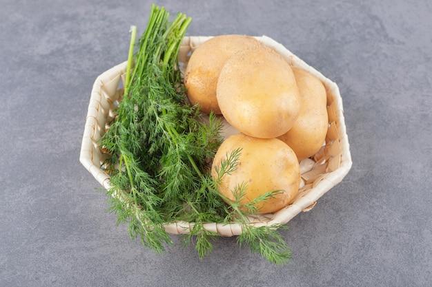 Biały talerz niegotowanych ziemniaków ze świeżym koperkiem