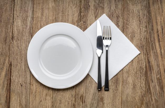 Biały talerz, nóż i widelec w serwetce na drewnianym
