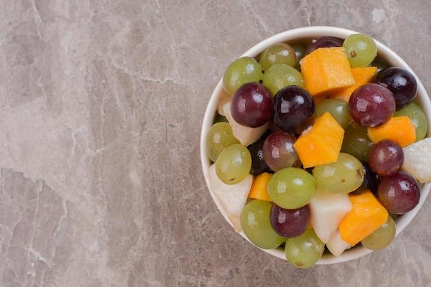 Biały talerz owoców na marmurowym stole.