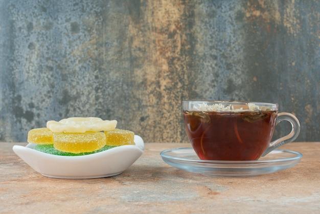 Biały talerz pełen cukierków galaretki cukrowej i filiżankę herbaty ziołowej