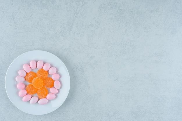 Biały talerz pełen słodkich pomarańczowych galaretek i różowych cukierków