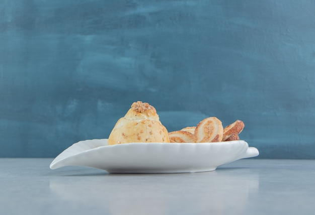 Biały talerz pełen słodkich pysznych ciasteczek z cukrem.
