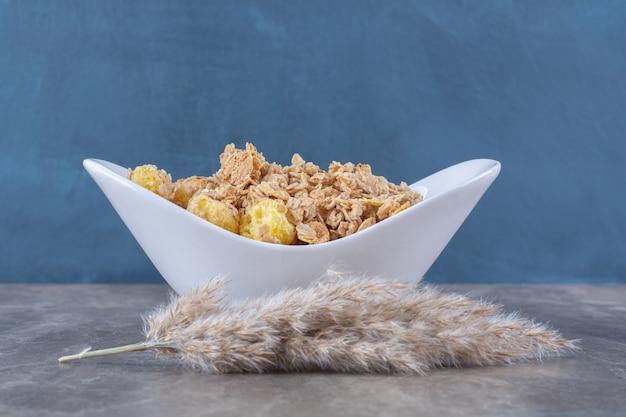 Biały talerz pełen zdrowych pysznych płatków kukurydzianych na szarym stole.