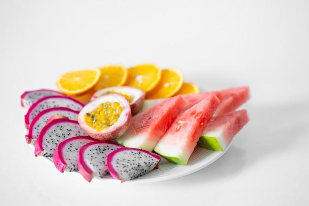 Biały talerz pokrojonych owoców. świeże owoce i witaminy.