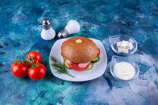 Biały talerz pysznego burgera i pomidorów na niebieskiej powierzchni.