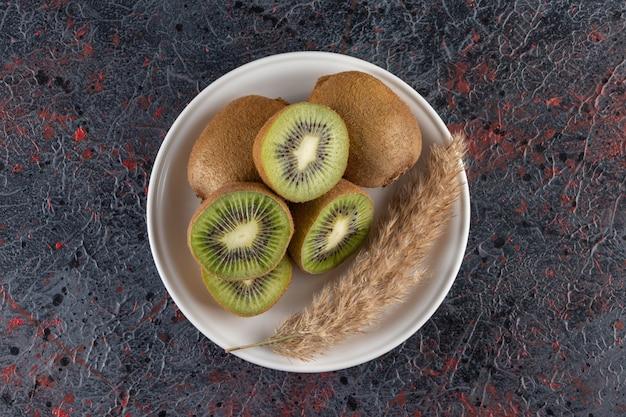 Biały talerz pysznych owoców kiwi na marmurowej powierzchni