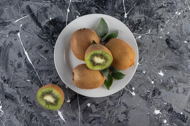 Biały talerz pysznych owoców kiwi na marmurowym stole.