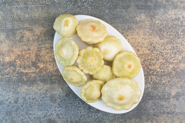 Biały talerz pysznych owoców na marmurowym tle. zdjęcie wysokiej jakości