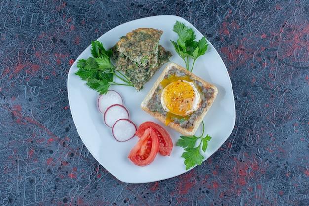 Biały talerz pysznych tostów z mięsem i warzywami.