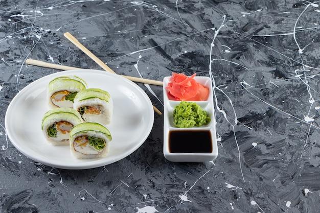 Biały talerz rolek sushi umieszczonych na marmurowym tle.