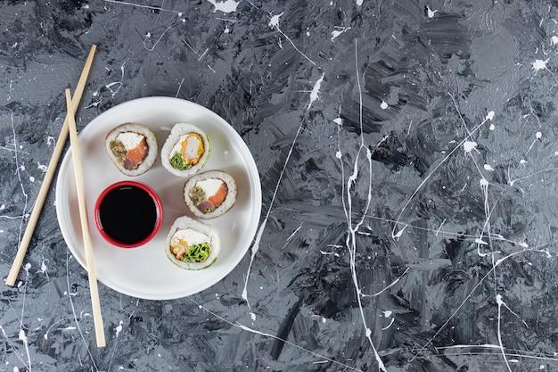 Biały talerz rolek sushi z tuńczykiem na tle marmuru.