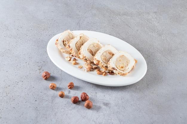 Biały talerz słodkich przysmaków z orzechami na kamiennym tle.