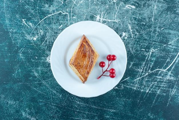 Biały talerz słodkiego pysznego ciasta na niebieskim tle. wysokiej jakości zdjęcie