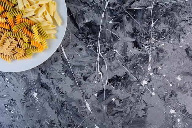 Biały talerz surowego, suchego wielobarwnego makaronu fusilli z makaronem penne