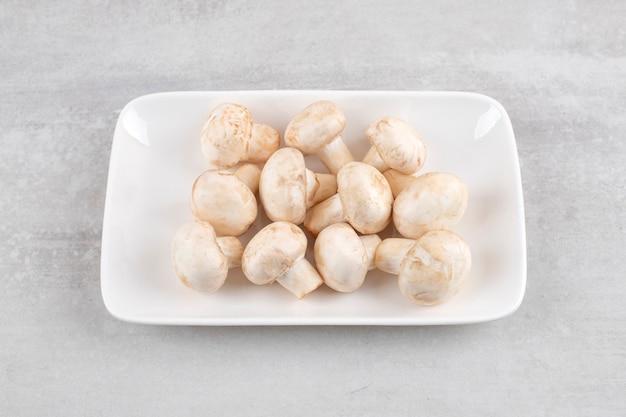 Biały talerz świeżych białych grzybów na kamiennym stole.
