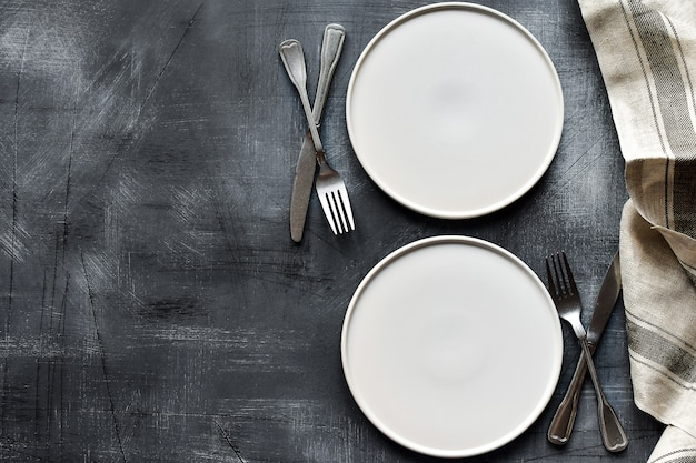 Biały talerz, sztućce i serwetka na ciemnym stole z kamienia. ustawienie tabeli