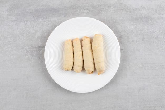 Biały talerz tradycyjnych słodkich mutaki na kamiennym stole.