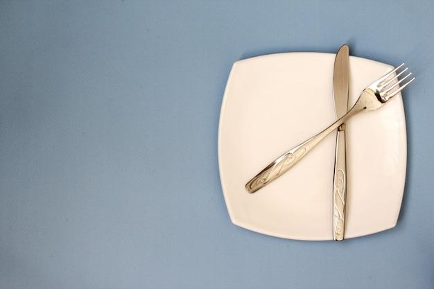Biały talerz widelec i nóż na niebieskim tle wyczyść talerz i sztućce na jasnym tle