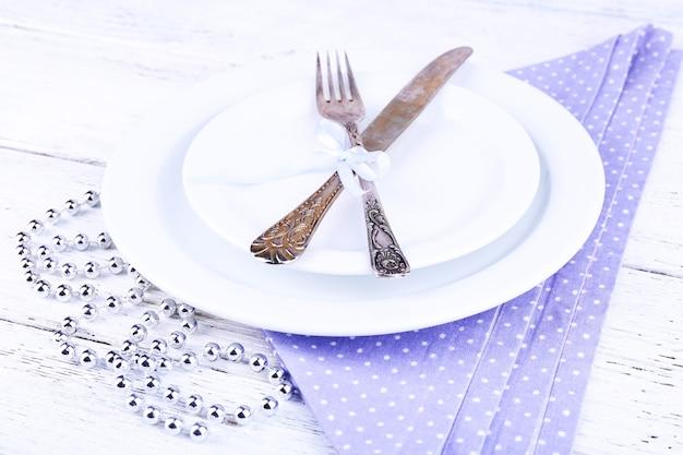 Biały talerz, widelec, nóż i świąteczne dekoracje na liliowej serwetce w kropki na drewnianym tle