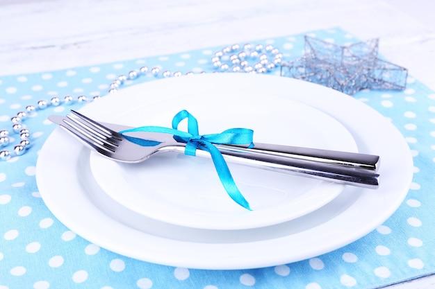 Biały talerz, widelec, nóż i świąteczne dekoracje na serwetce w kropki na drewnianym tle