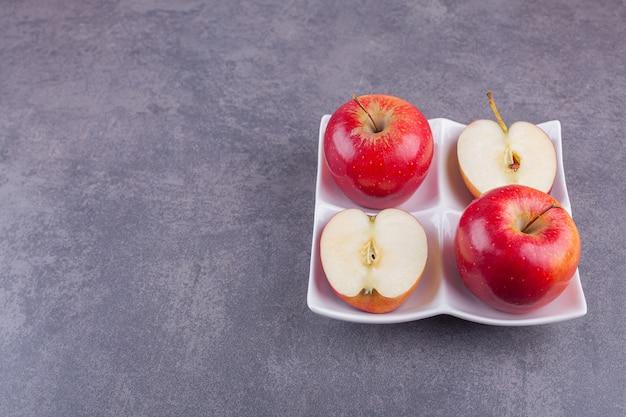 Biały talerz z błyszczącymi czerwonymi jabłkami na kamiennym tle.