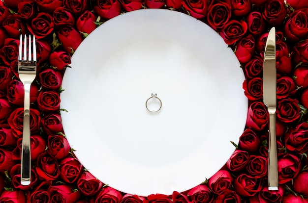 Biały talerz z brylantowym pierścionkiem na różach, jadalnia na walentynki.