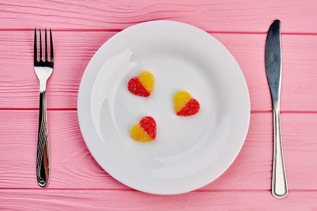 Biały talerz z cukierkami w kształcie serca. talerz z trzema galaretkowymi sercami, widelcem i nożem na różowym tle drewnianych. koncepcja walentynki.