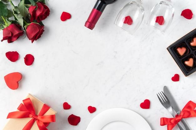 Biały talerz z czerwonym kwiatem róży na marmurowym białym tle stołu na walentynki randkowy świąteczny posiłek.