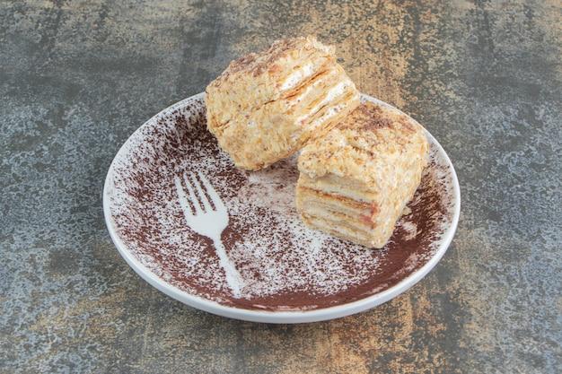 Biały talerz z dwoma kawałkami ciasta napoleona i kakao w proszku