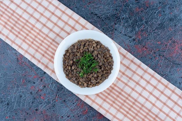 Biały talerz z fasolą i ziołami na obrusie.