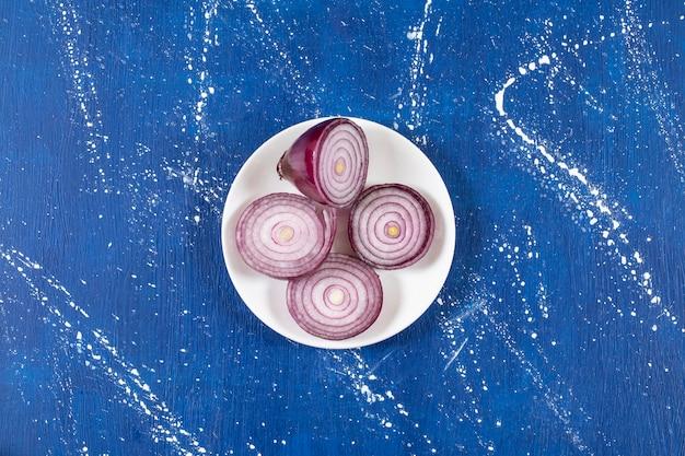 Biały talerz z fioletowymi krążkami cebuli na marmurowej powierzchni