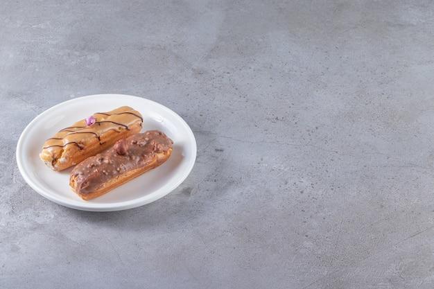 Biały talerz z karmelowo-czekoladowymi eklerami na kamiennej powierzchni