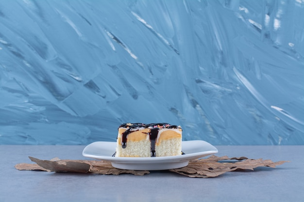 Biały talerz z kawałkiem pysznego kremowego ciasta.