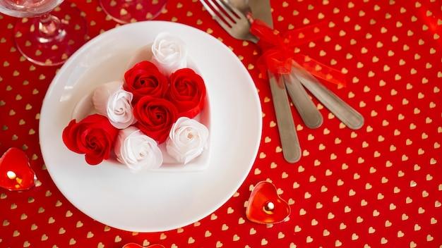 Biały talerz z nożem i widelcem na jasnym czerwonym tle. dekoracja czerwonych i białych róż. nakrycie stołu na walentynki
