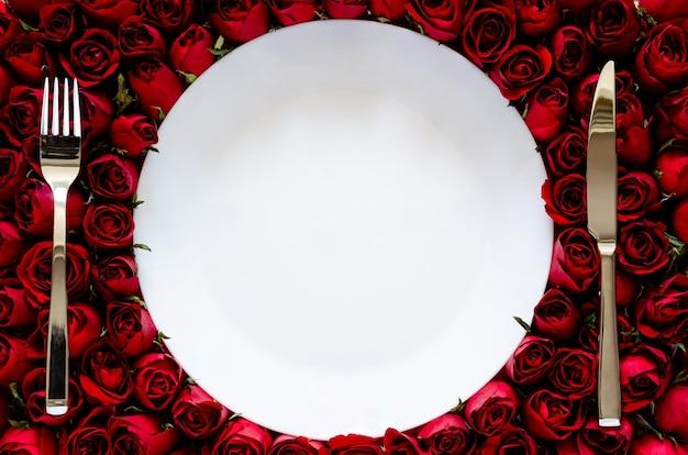Biały talerz z nożem i widelcem na tle róż do jadalni na rocznicę lub walentynki koncepcja.