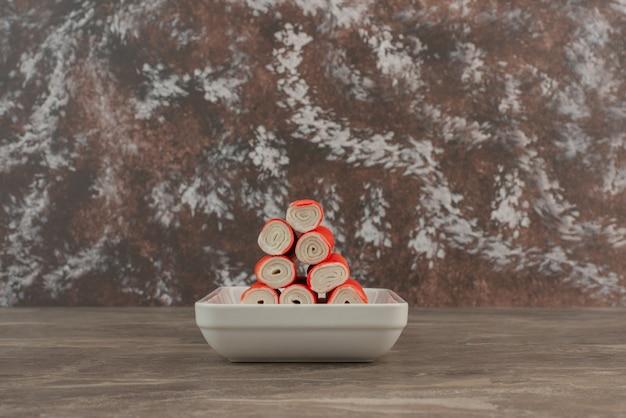 Biały talerz z paluszkami krabowymi.