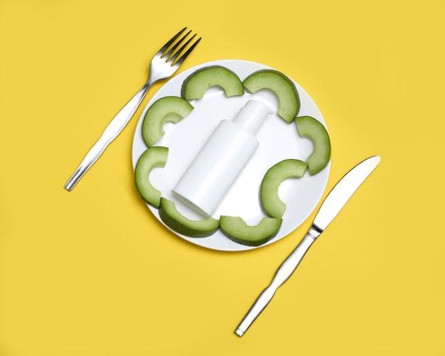 Biały talerz z pojemnikiem na kosmetyki butelka z plastrami awokado podawana z nożem i widelcem.