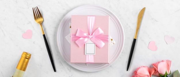 Biały talerz z prezentem i różowym kwiatem róży na marmurowym tle białego stołu na specjalne święto randkowe posiłek w walentynki.