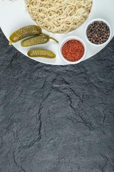 Biały talerz z pysznym makaronem i marynowanymi korniszonami.