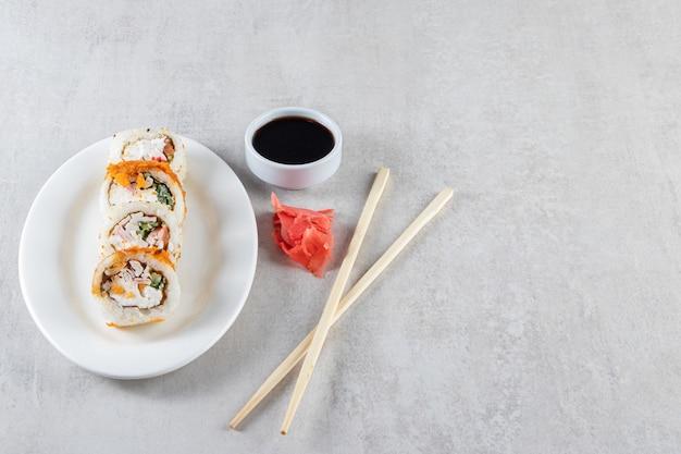 Biały talerz z rolkami sushi i sosem sojowym na kamiennym tle.