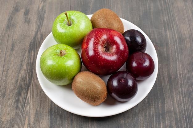 Biały talerz z różnymi soczystymi owocami na drewnianym stole. wysokiej jakości zdjęcie