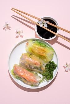 Biały talerz z sajgonki, pałeczkami, sosem sojowym i kwiatami wiśni