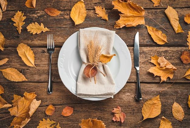 Biały talerz z serwetką i sztućcami na drewnianym tle z jesiennymi liśćmi