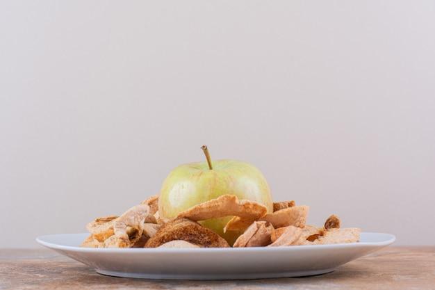 Biały talerz z suchymi krążkami jabłkowymi i świeżym zielonym jabłkiem na marmurowym stole. wysokiej jakości zdjęcie