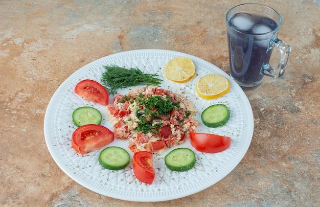 Biały talerz z warzywami i szklanką soku.