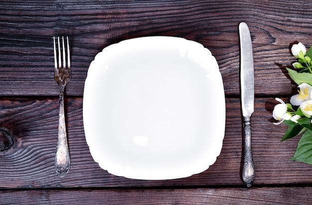 Biały talerz z żelaznym widelcem i nożem