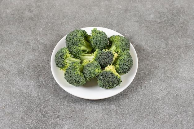 Biały talerz zdrowych świeżych brokułów na kamiennym stole.