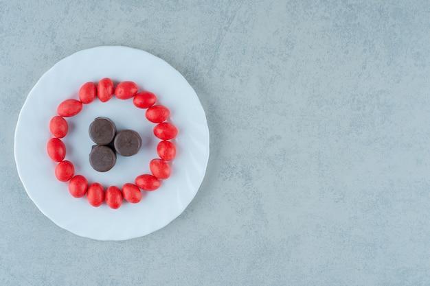 Biały talerz ze słodkimi czerwonymi cukierkami i czekoladowymi ciasteczkami na białej powierzchni