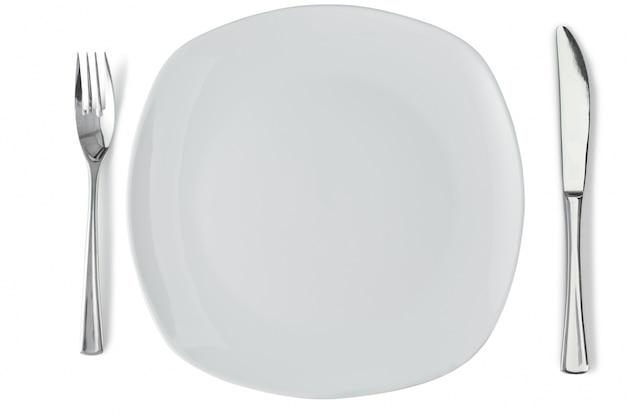 Biały talerz ze srebrnym widelcem i nożem